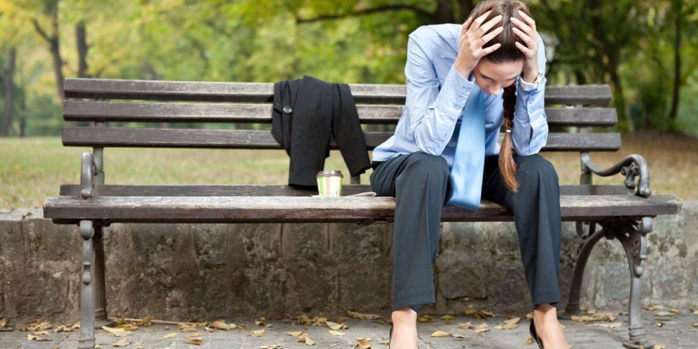 11508547 - worried caucasian businesswoman sitting on bench in park
