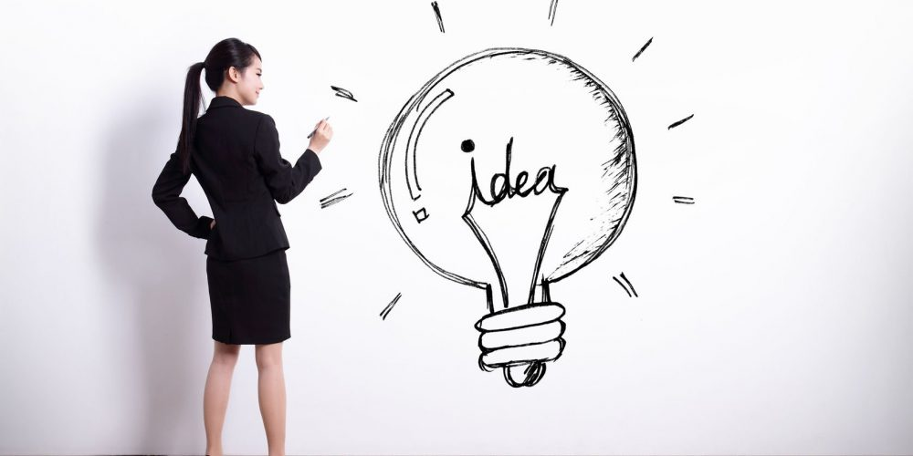 40293895 - idea concept - back view of business woman writing idea and light bulb on white wall background